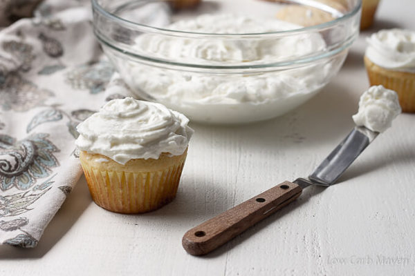 A cupcake slathered in whipped cream cheese frosting sits between a floral napkin and a small spatula with frosting with a glass bowl of cream cheese frosting and frosted cupcakes behind.