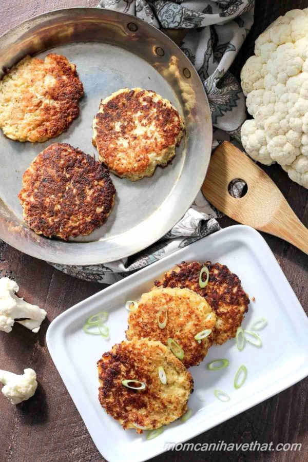 Top down photo of Cauliflower fritters or low carb hash browns stacked off-set on a white rectangular plates and in a pan with a wooden spatula to the side and pieces of raw cauliflower arranged around the plate and pan.