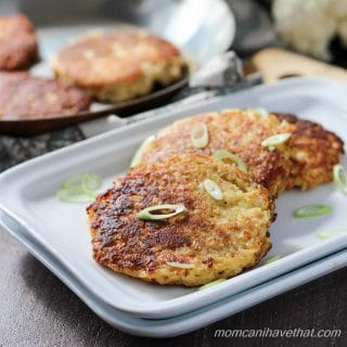 Cauliflower fritters or low carb hash browns stacked off-set on a white rectangular plates, garnished with green onions, and a skillet with more fritters behind with pieces of raw cauliflower in the background.