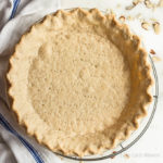Baked low carb pie crust with fluted edge and dock marks in a pie plate on a round wire cooling rack with a blue and white kitchen towel to the left and sliced almonds around the marble surface.
