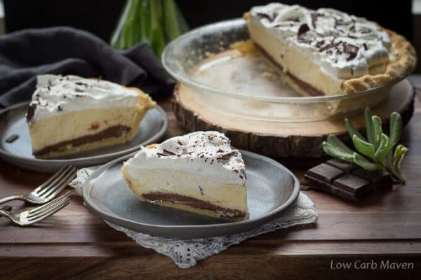 A slice of low carb black bottom pie featuring a layer of chocolate custard and an airy layer of chiffon filling topped with whipped cream and chocolate shavings placed on a rustic gray plate on a lacy edged napkin. Another slice of pie and a partial pie in a clear pie plate are behind.
