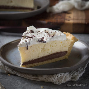 A slice of low carb black bottom pie, featuring a layer of chocolate custard and an airy chiffon layer topped with whipped cream and chocolate shavings on a dark gray plate placed on a folded white napkin with a wooden tray behind.
