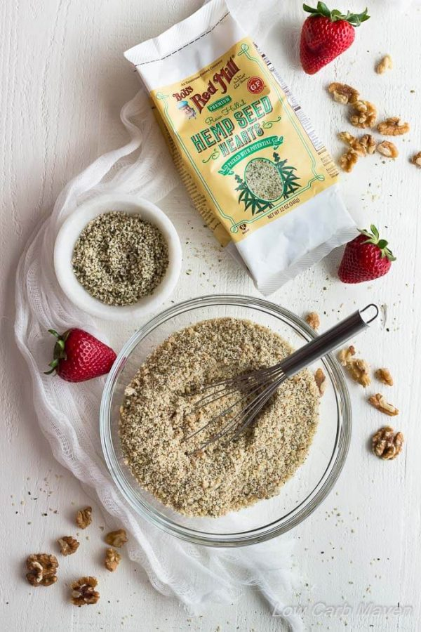 Ingredients for low carb hemp walnut pie or tart crust featuring ground hemp seeds and walnuts in a bowl, toasted walnuts on a marble surface with fresh strawberries and a package of Bob's Red Mill Hemp Seeds.