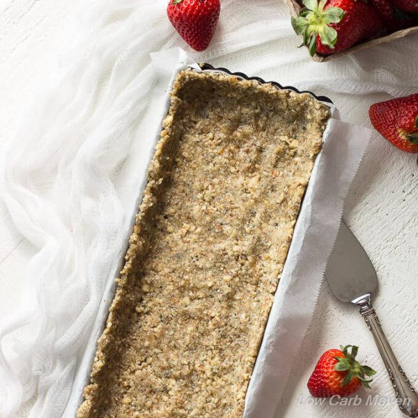 Hemp walnut crust pressed into a parchment lined rectangular tart pan with a sliver pie server to the right, a white cheesecloth to the left and fresh strawberries around.