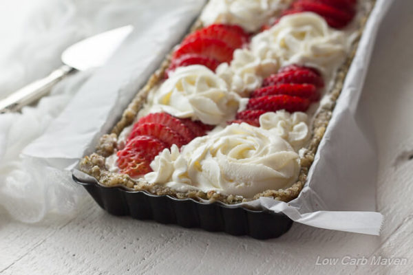 A closeup of a strawberry dessert tart with cream cheese tart featuring a hemp and walnut crust in a black rectangular tart pan lined in white parchment decorated with sliced fresh strawberries and piped cream cheese roses.
