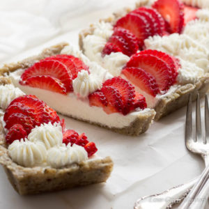 A closeup view of a sliced cream cheese and goat cheese strawberry tart in a press-in hemp and walnut crust with fresh strawberries arranged nicely among piped stars on top. The tart is on a piece of white parchment with silver forks in front to the side and a piece of white cheesecloth in the background.