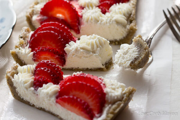 Close-up overhead view of a slice low carb strawberry cream cheese tart in a hemp walnut crust decorated with sliced strawberries and piped cream cheese stars.
