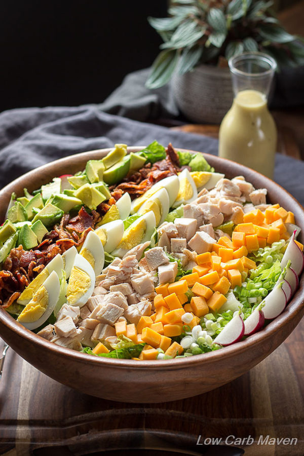 A Cobb salad with avocado, bacon, hard boiled eggs, diced chicken, cheddar cheese, green onion and quartered radishes all laid out in rows in a wooden salad bowl with a gray napkin behind and to the left and a carafe of Cobb salad dressing to the right.
