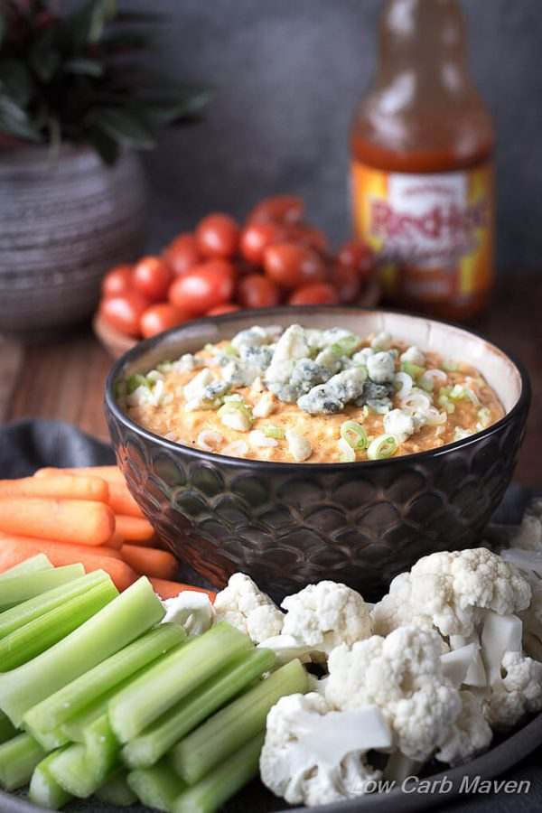 Buffalo Chicken dip topped with scallions and blue cheese in a bowl with raw vegetables and Frank's Red Hot Buffalo Sauce.