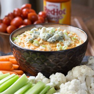Buffalo Chicken dip topped with scallions and blue cheese in a brown bowl in the middle of a vegetable try with cauliflower, celery, and carrots with a bowl of grape tomatoes in the background and a bottle of Frank's Red Hot Buffalo Sauce to the right.