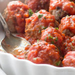 Low carb Italian meatballs in Marinara sauce and sprinkled with parsley in a white scalloped dish with a sauced spoon in a place where a meatball once sat.