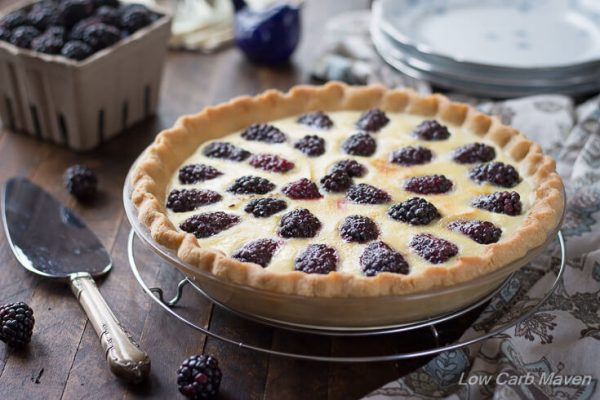Beautifully browned custard pie with blackberries and fluted crust in a glass pie plate sitting on a round wire rack with blackberries and a silver pie server to the left, a pint of berries and china dessert plates behind and a blue and brown floral napkin to the right.