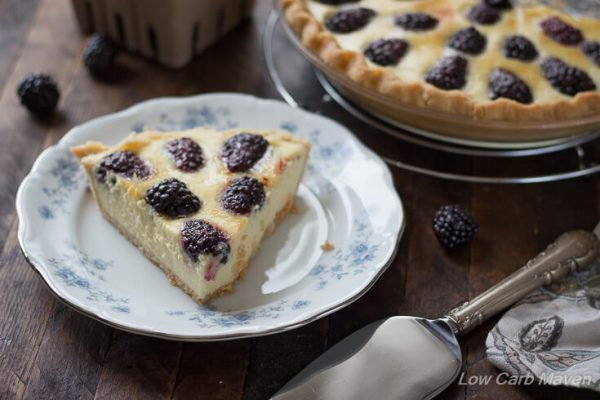 A slice of blackberry custard pie (no-bake buttermilk pie) on a blue and white floral china plate with a silver pie server to the right and the whole pie behind, with fresh blackberries on the wooden table.