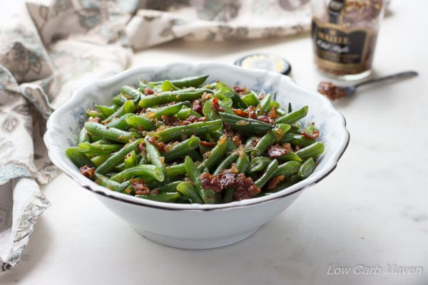 Sweet and sour German green beans with bacon, onions and whole mustard seeds in a white bowl.