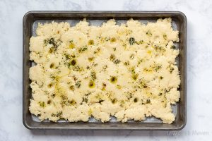 Low carb almond focaccia dough topped with olive oil dipping sauce in a sheet pan before baking.