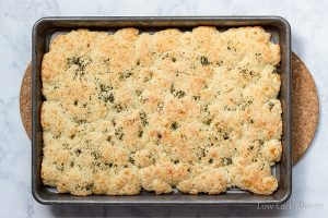 Almond flour focaccia topped with herbs in a sheet pan.