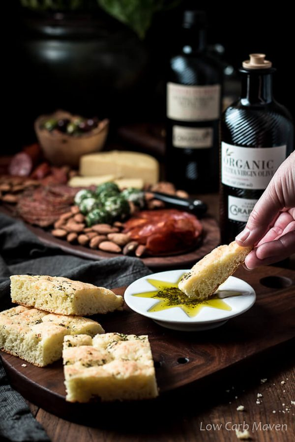 Action shot: dipping a piece of low carb focaccia into olive oil dipping sauce with more pieces of focacccia to the left on a cutting board and a bottle of Carapelli Organic Extra Virgin OlIve Oil behind and a low carb charcuterie board in the background.