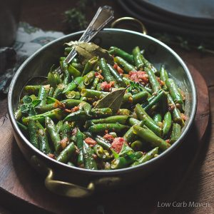 Mexican green beans with tomatoes, oregano and bay leaf in a copper gratin pan with brass handles.