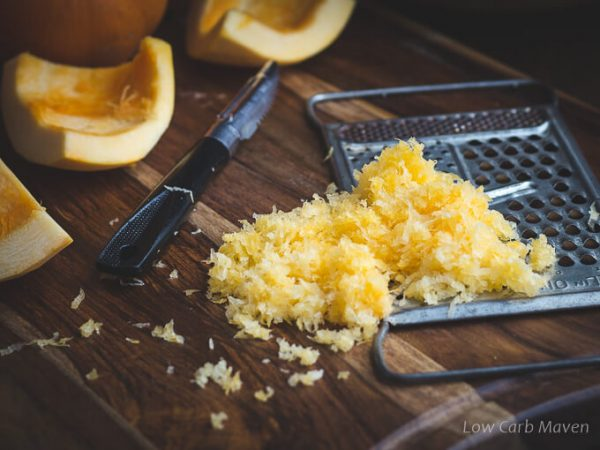 Fresh grated pumpkin with grater, peeler and cut and whole pumpkins.