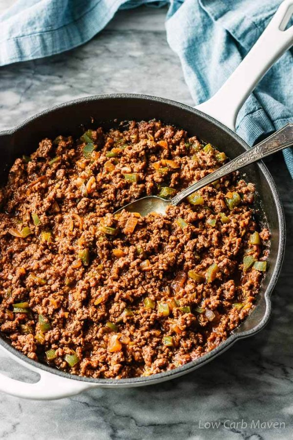 Homemade sloppy joes meat with green bell peppers and onions in a pan with serving spoon.