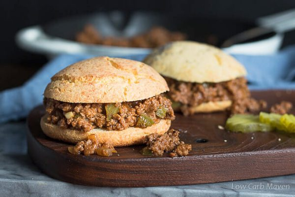Homemade sloppy joes meat with green pepper and onions in sauce on low carb hamburger buns on a cutting board with pickles. Sugar free recipe.
