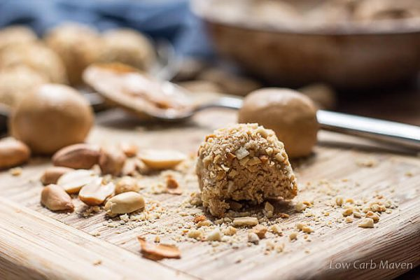 low carb peanut butter balls rolled in chopped peanuts on a cutting board.