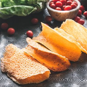 cheddar cheese taco shells on a tray with tomatoes and lettuce