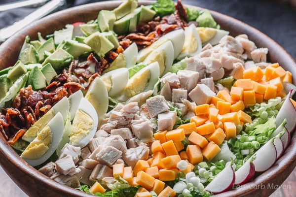 Chicken Cobb salad with toppings in a wooden salad bowl.