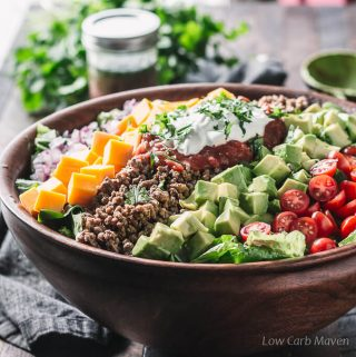 Healthy low carb taco salad with ground beef, salsa and sour cream in a wooden bowl.