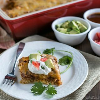 A serving of Mexican chicken casserole with sour cream, avocado, tomato and cilantro on a plate with a fork.