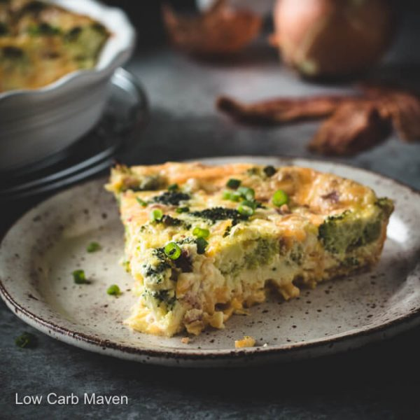 Slice of broccoli cheddar quiche with bacon on a plate.