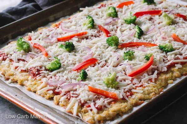 Chicken crust pizza with cheese and vegetables in a sheet pan.