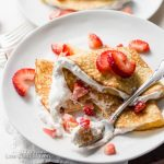 Folded coconut flour crepes with strawberries and whipped cream on a plate with fork.