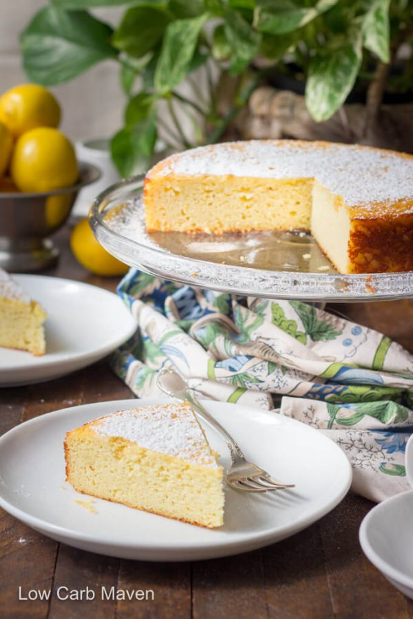 Italian lemon ricotta cake on cake stand. Slices of cake on white plates with colorful napkin to the side and lemons behind.