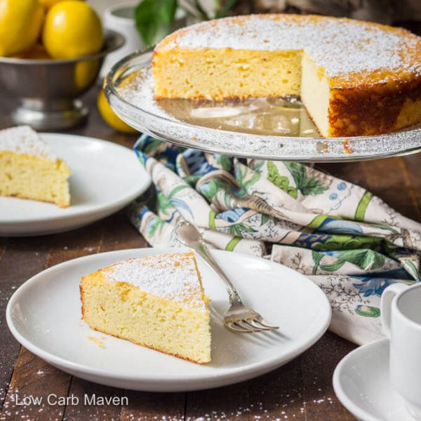 Lemon ricotta cake on cake stand and slice on plate with lemons.