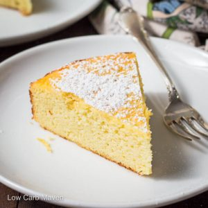 Slice of lemon ricotta cake with powdered sugar on a white plate with fork.