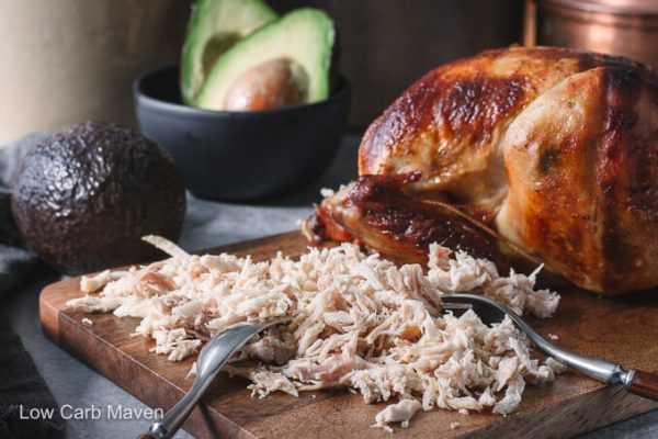 Shredded rotisserie chicken for chicken enchiladas on a cutting board with fork and avocados.