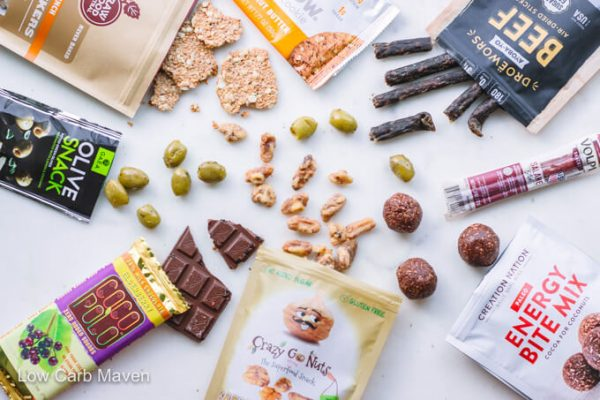 Keto Krate subscription box products: Cookie, beef jerky, meat stick, protein bites, walnuts, chocolate bar, olives, flax crackers.