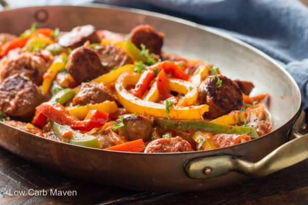 Italian sausage and colorful bell pepper strips in an oval casserole dish.