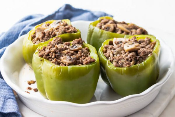 Green bell peppers stuffed with ground beef, mushrooms and onions for Philly cheesesteak stuffed peppers.