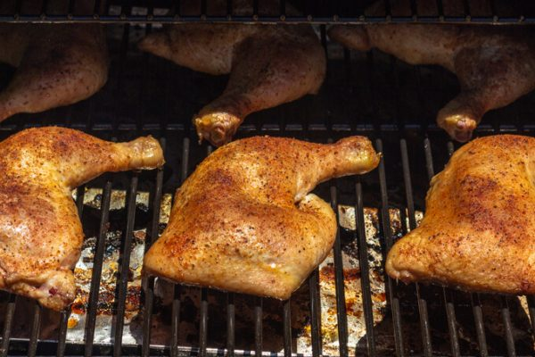 Smoked chicken leg quarters with dry rub on a pellet grill.