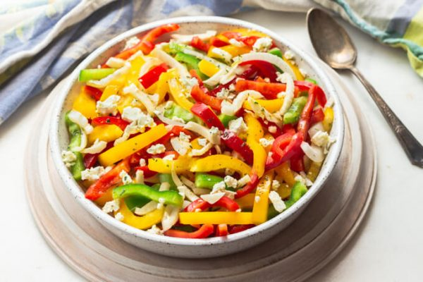 Colorful bell pepper salad with onions and feta.