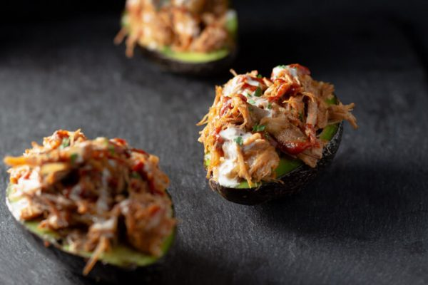 Pulled pork stuffed avocados with cheese.