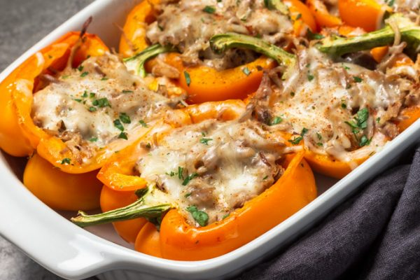 Pulled pork stuffed peppers with cheese in a baking dish.