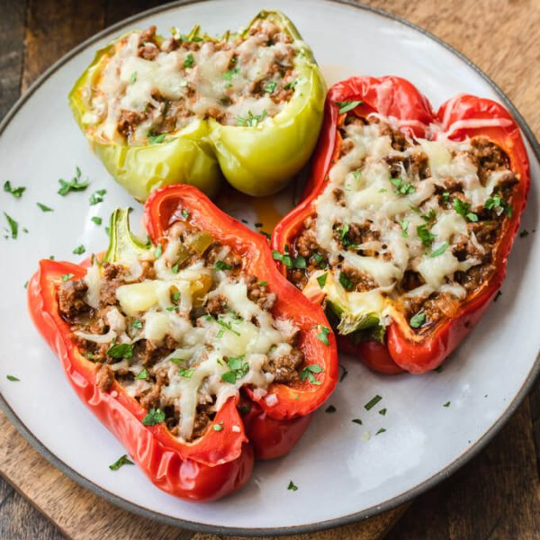 Sloppy Joe stuffed bell peppers top with cheese on a plate.