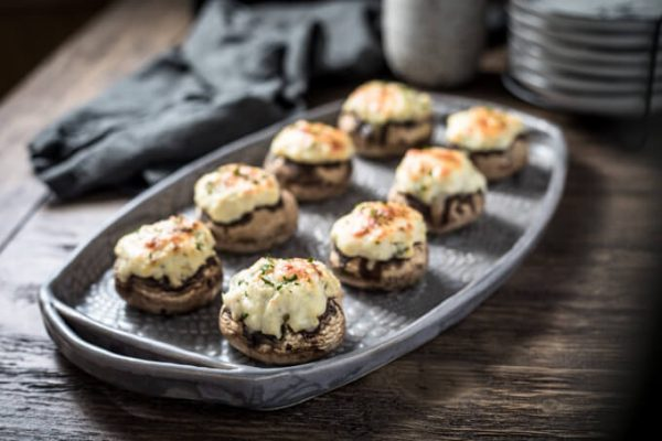Creamy crab stuffed mushrooms with cream cheese on a platter.