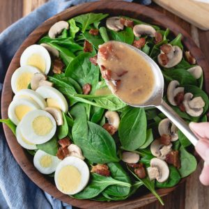 Spinach salad with warm bacon dressing with hardboiled eggs and mushrooms.