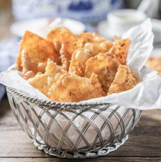 Crispy chicken skin chips in a paper lined basket.