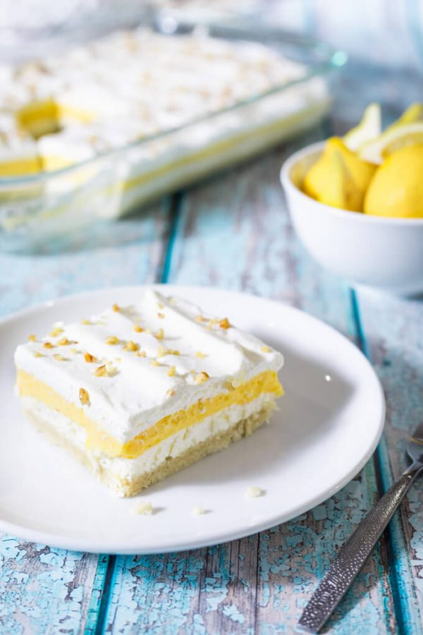 Lemon lush layered dessert with pecans on top.