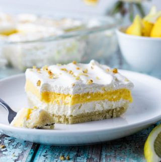 Lemon lush layered dessert on a plate with fork.